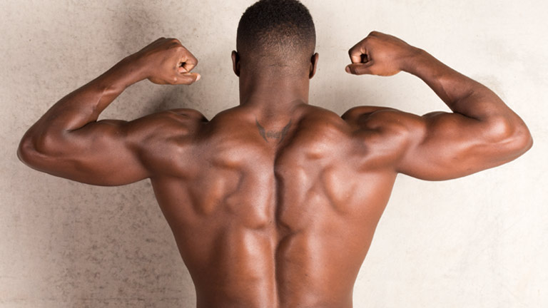 Harry Aikines Aryeetey, GB Olympic sprinter and ambassador of The Gymbook. Here Harry is tensing his back for a photoshoot to promote his Get Explosive 10 week fitness plan.